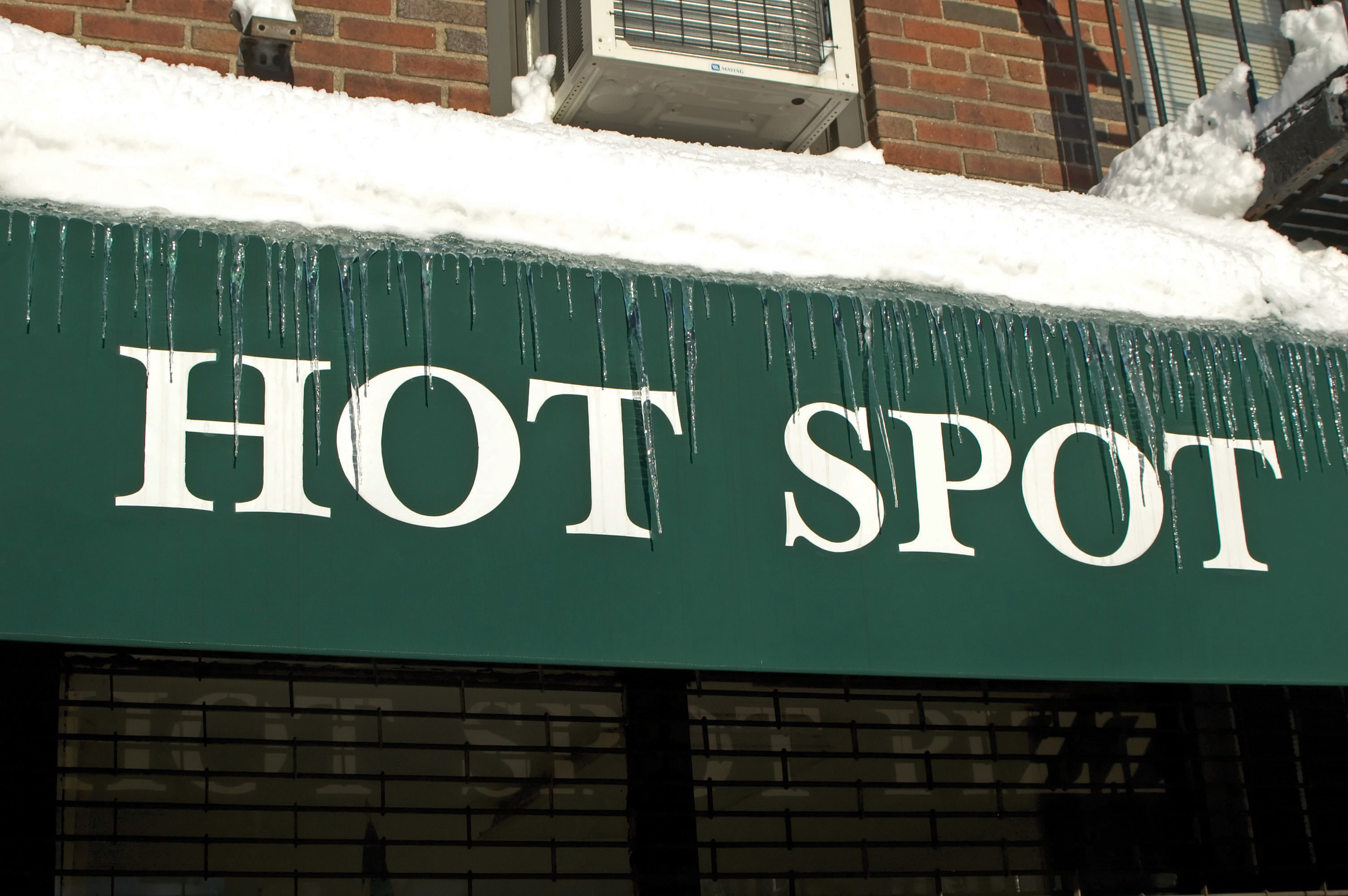 "A sign covered in icicles that reads ""Hot Spot"""